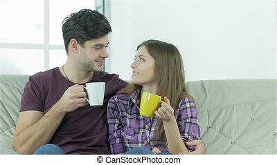 Couple looking at each other while sitting on a sofa with cups