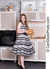Happy ordinary woman with pan at her kitchen
