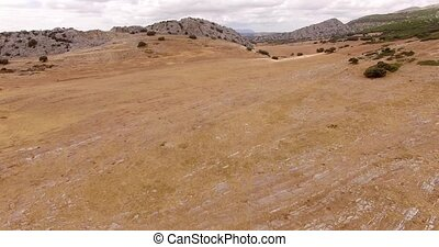 Aerial Drone Flight Over Dry Field of Grass in Mountains