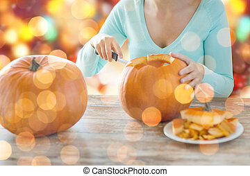 close up of woman carving pumpkins for halloween - holidays,...