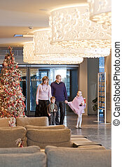 Family in the hotel - Happy family walking at foyer in the...