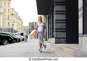 happy pregnant woman with shopping bags at city - pregnancy,...