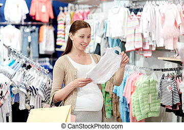 happy pregnant woman shopping at clothing store - pregnancy,...