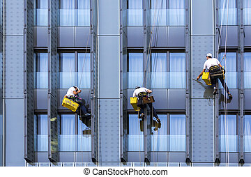 Three window washers - Three climbers wash windows and glass...