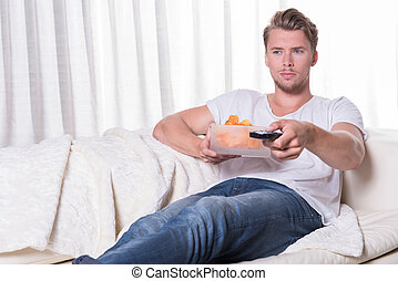 Portrait young man sitting on couch and eating chips and...