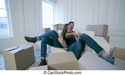 Couple in love hugging lying down among the boxes - Moving,...