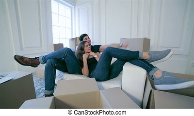 Couple in love lying on sofa among boxes - Moving home and...