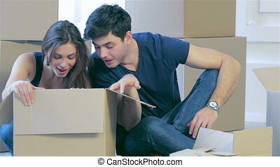 Couple in love pulls things out of boxes - Moving home and...