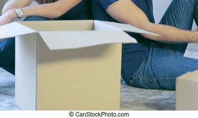 Couple sitting on the floor among the boxes and kiss -...