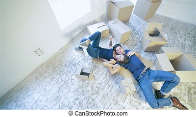 Couple girl and guy lie on the floor in an embrace - Moving,...