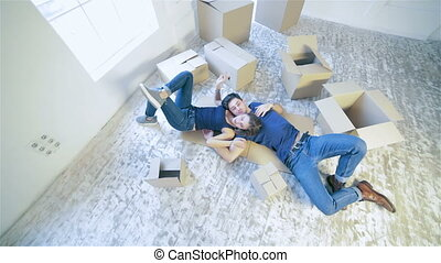 Couple lying on the floor among the boxes in an empty...