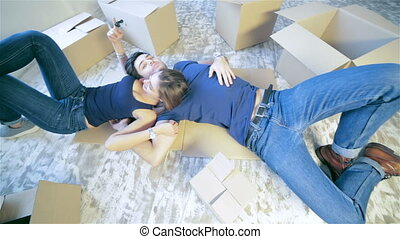 Among the boxes in an empty apartment - New life. Couple...