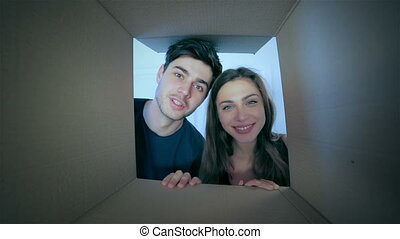 Smiling man and woman in love look into boxes - Moving,...