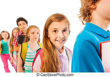 Girl in the line smiling among other students - Group of...
