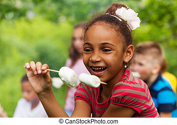 Happy African girl holding stick with marshmallow - Happy...