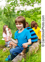 Positive small boy holding stick with marshmallows during...
