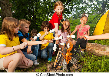 Kids sitting near bonfire with marshmallow during camping in...