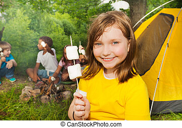 Close-up of girl holding stick with marshmallows near tent...