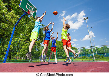Children jump for flying ball during basketball game on the...
