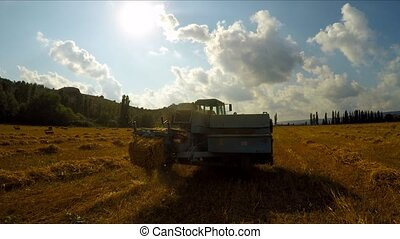 Tractor With Trailer Making Hay Bales - Rear shot of rural...