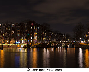 amsterdam canal at night - illuminated amsterdam canal and...