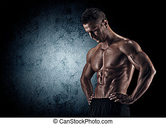 Muscular man in studio on dark background - Muscular young...