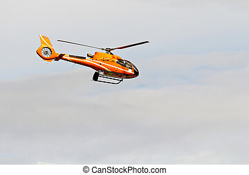 Civilian helicopter flying in the sky with blur propeller