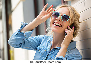 Cute blonde talking on a cell phone - Cute blonde in...