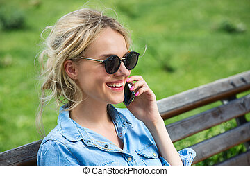 Cute blonde talking on a cell phone - Closeup portrait of...