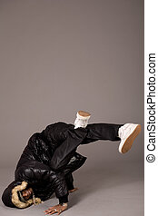 Handsome black man trying head stand on grey background