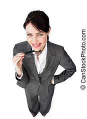Self-assured businesswoman holding glasses isolated on a...