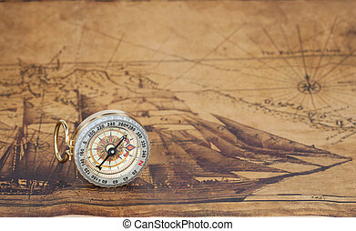 Vintage compass lies on an ancient map
