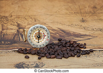 Vintage compass and bean lies on an ancient map