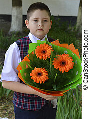 the school student with a bouquet of bright flowers near school