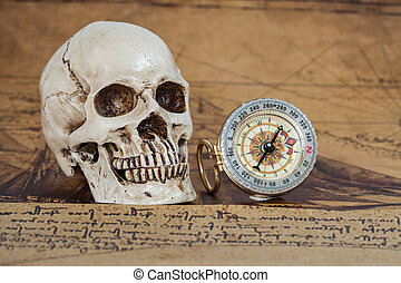 Human Skull and compass on Old map Background