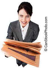 Assertive businesswoman reading a newspaper
