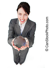 Smiling businesswoman holding a crystal ball isolated on a...