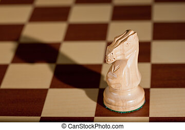 Chess piece - a white knight on a chessboard