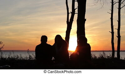People silhouettes at sunset a clear summer night - People...