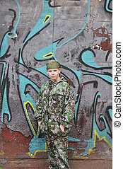 boy teenager in a camouflage and with equipment for...