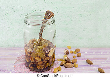 Jar of honey with choped nuts, almond and hazelnuts Healthy...