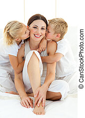 Adorable siblings kissing their mother sitting on a bed at...