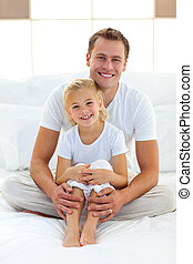 Blissful father playing with his girl on a bed at home