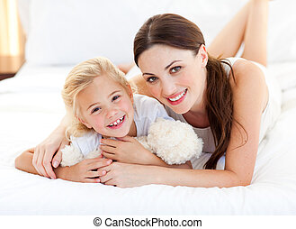 Portrait of a smiling mother and her little girl lying on...