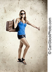Beautiful young woman hitch hiking with old leather suitcase...