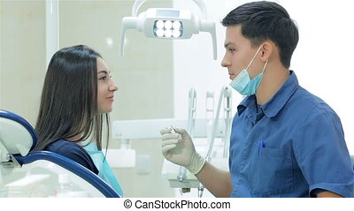 Dentist holding a tool and explains the girl patient