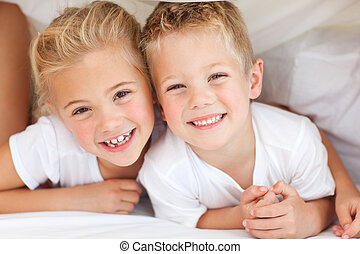 Adorable siblings playing on a bed at home