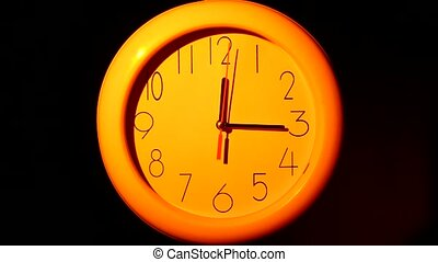 Icon of orange clock with shadow on black background, night...