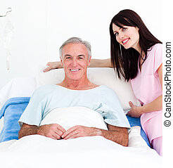 Beatiful female nurse adjusting pillows for a senior patient...