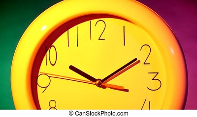 yellow clock on colorful background - close up of an white...